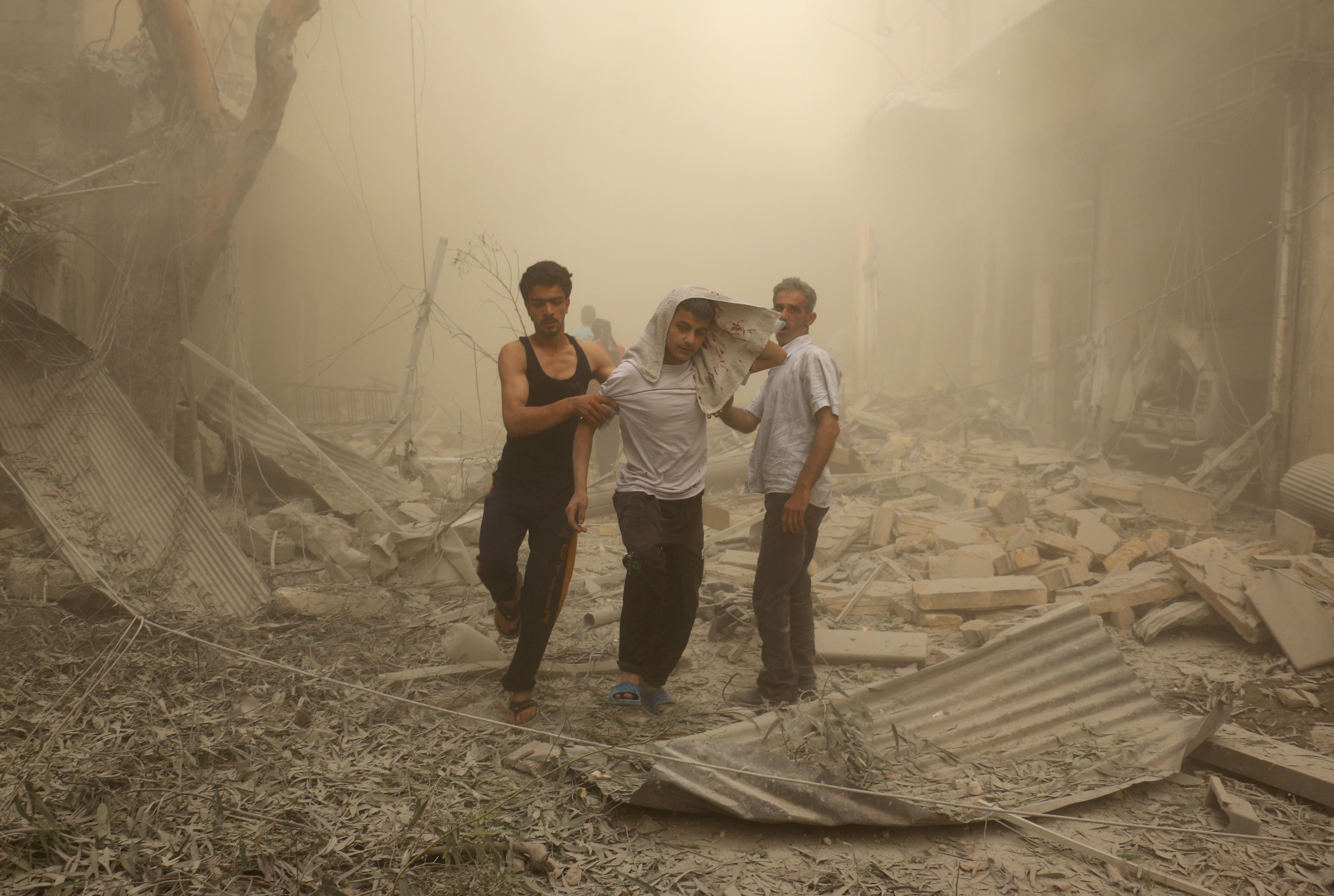 Syrians help a wounded youth after an airstrike on the al Fardous rebel-held neighborhood of Aleppo.