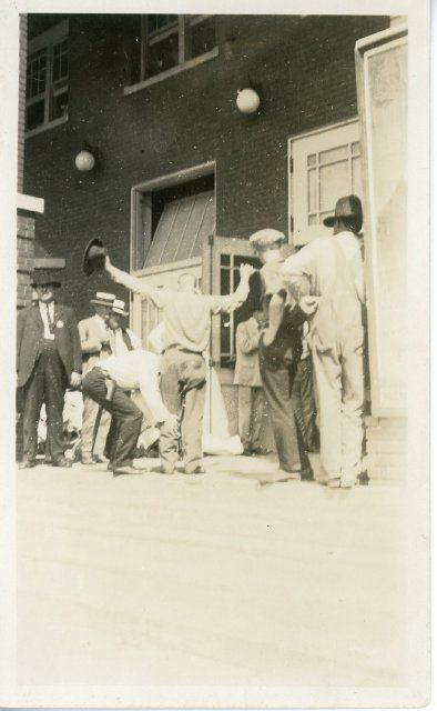 A black man holds up his arms while he is being searched by a white man during the Tulsa race riot on June 1, 1921. A group o