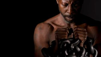 A shirtless black man, looking down at his hands, which are trapped between heavy metal chains. The man is spot lit from the side, and shot against a black background.