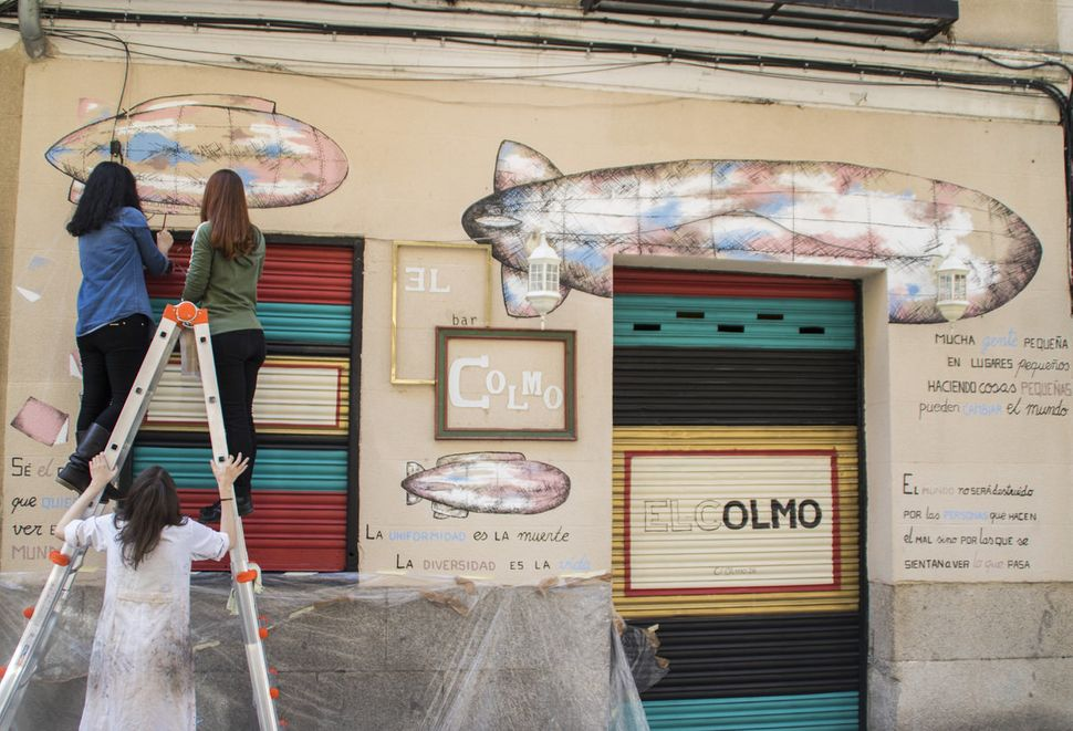 Artists cover the facade of the bar El colmo with illustrations of zeppelins, books, and quotes by the likes of Victor Hugo,