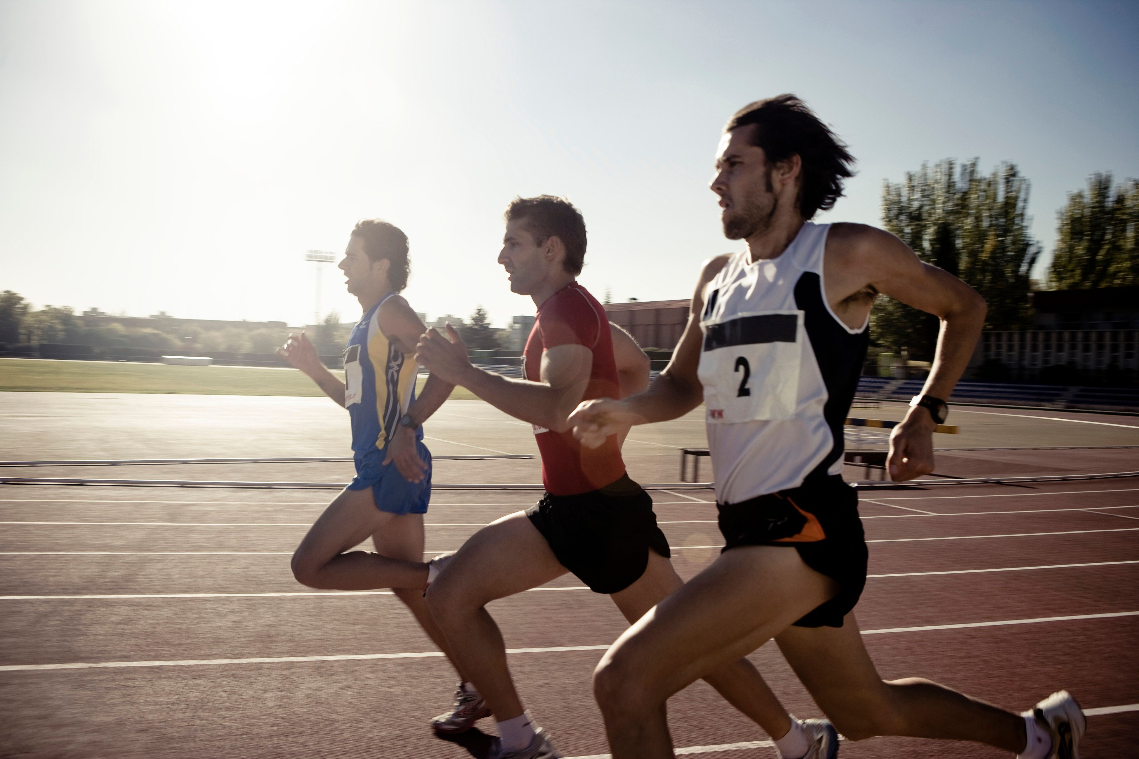 Male athletes running on race track, side view