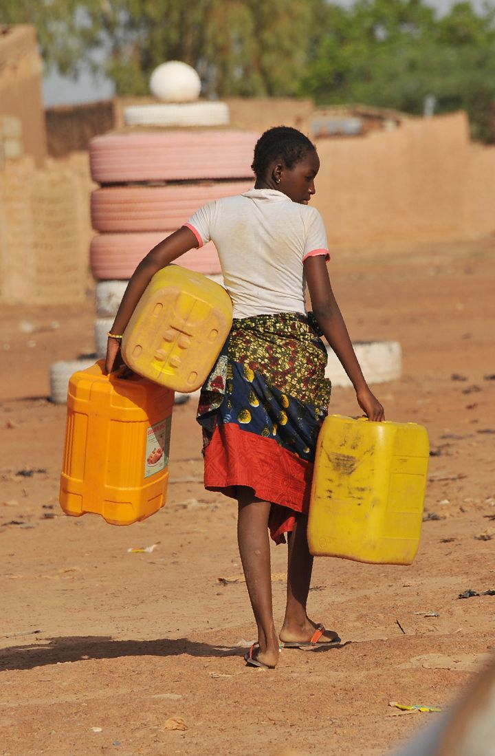A girl carries plastic jugs to collect water in the poor district of Taptenga suburb of Ouagadougou on May 4, 2016. Burkina F