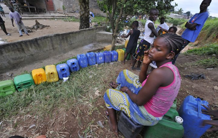 A girl sits on a canister while other locals wait to collect drinking water on August 10, 2010 in Abobo, a poor neighborhood