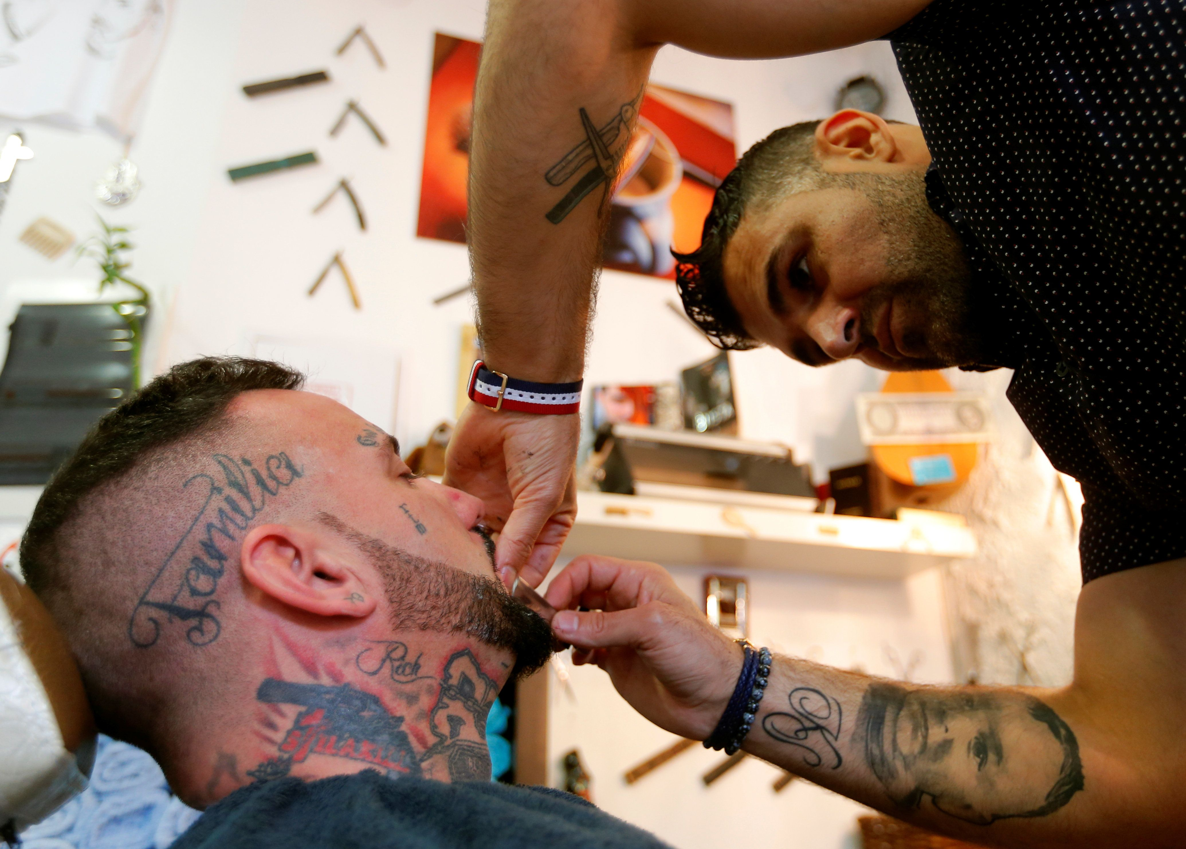Ibrahim Haji Mohammad, a Kurdish refugee from Syria, trims a beard of a client in his barber's shop in Budapest, Hungary, May 24,2016. REUTERS/Laszlo Balogh