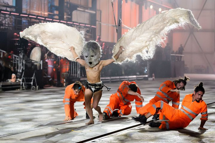 A shirtless performer wearing large wings is seen during Wednesday's opening ceremony for the NEAT Gotthard Base Tunnel.