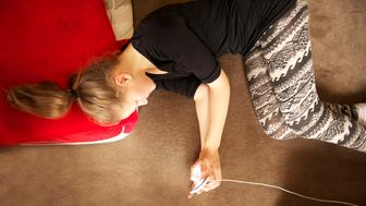 Fourteen-year-old teenage girl lying on floor cushions looking intently at her phone, which is connected to a charger.