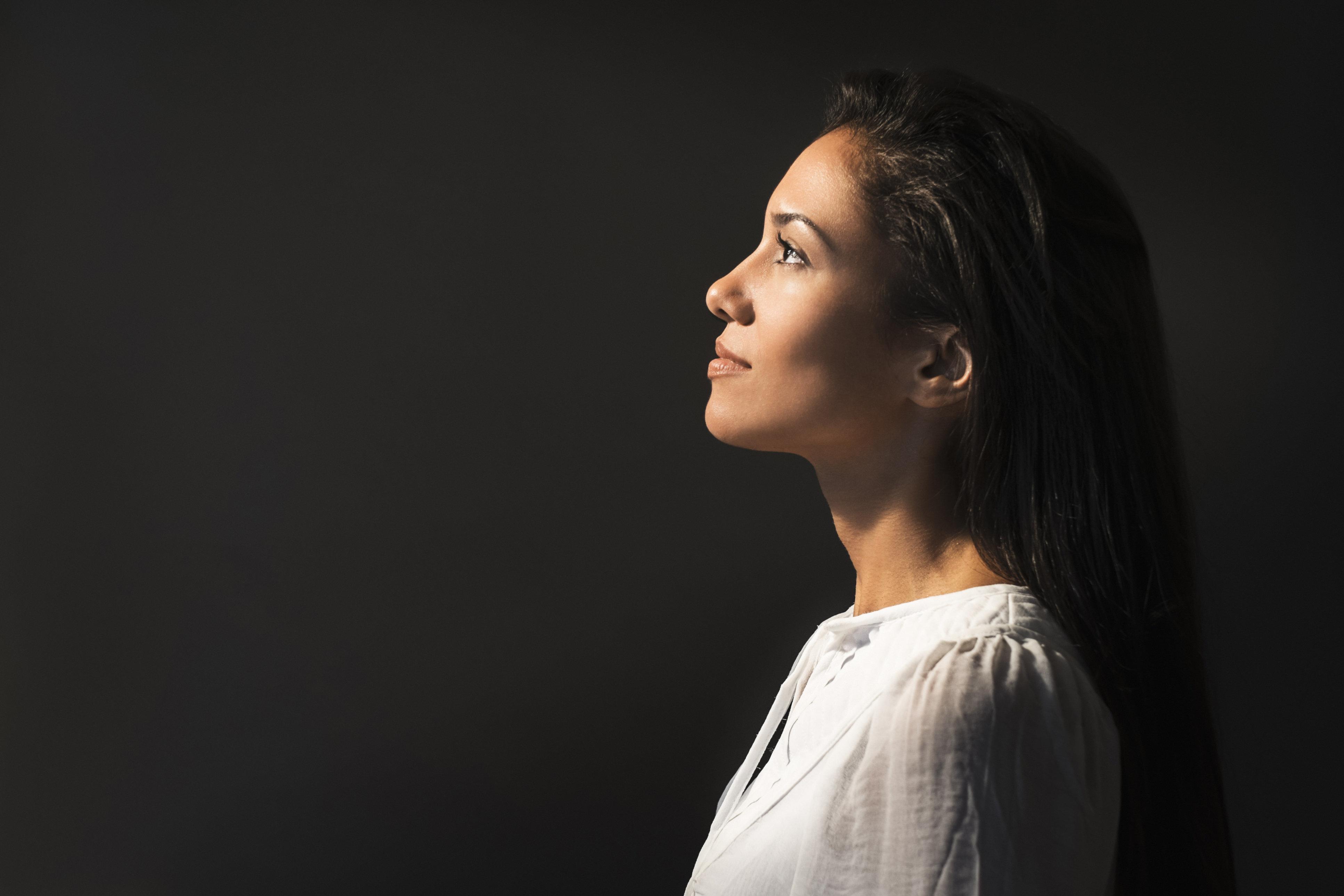 Hispanic woman looking up into light