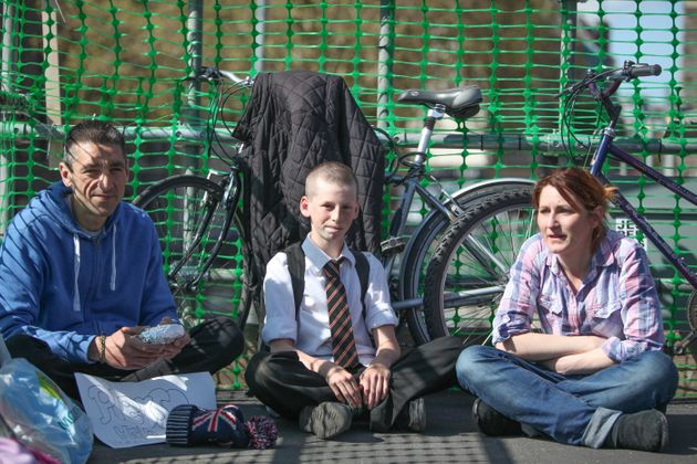 Hamish sits besides Paul Abbasi, left, and Ginna Shandur, right, who receive his