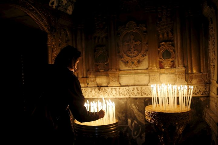 An Armenian woman lights a candle in Jerusalem on April 24, 2015, during a mass marking the 100th anniversary of the Arm