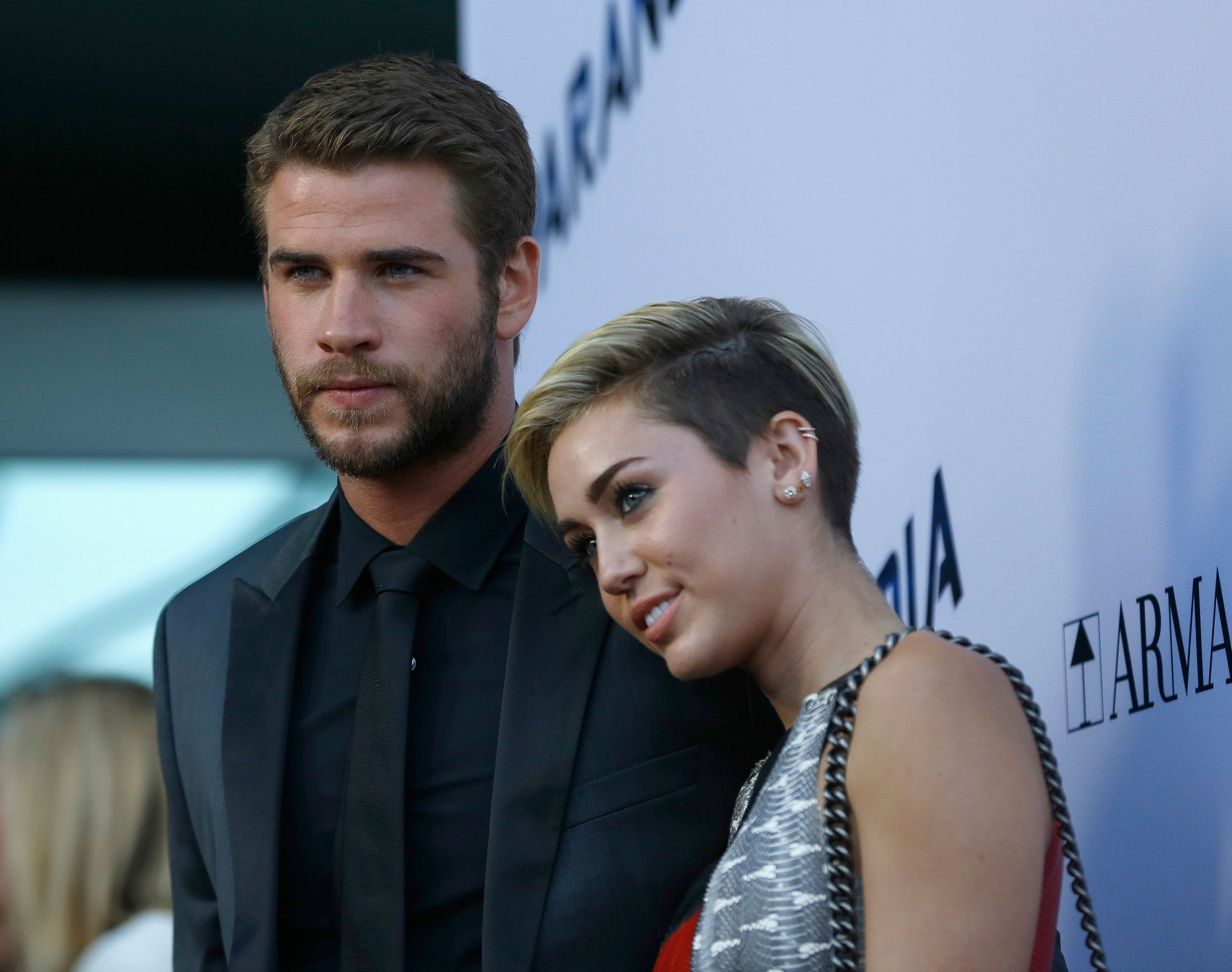 "Cast member Liam Hemsworth poses with his fiancee, singer Miley Cyrus (R), at the premiere of ""Paranoia"" in Los Angeles, California August 8, 2013. The movie opens in the U.S. on August 16.   REUTERS/Mario Anzuoni  (UNITED STATES - Tags: ENTERTAINMENT)"