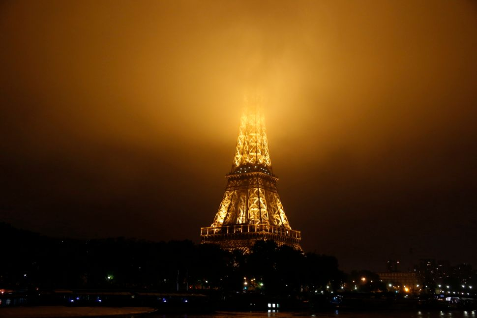 Fog covers the top of the Eiffel Tower.