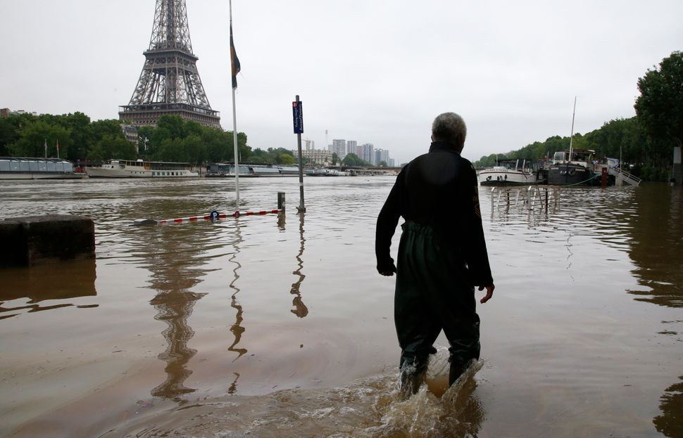 A man trudgesthrough floodedstreets in centralParis.