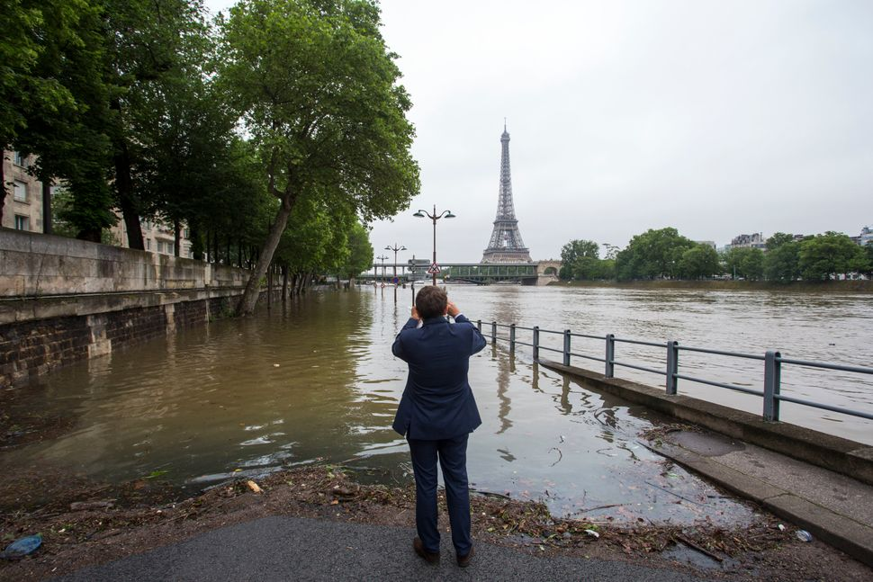 A manphotographsthe flooding river.