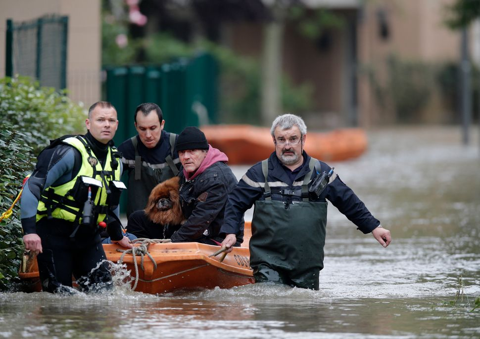 French firefighters evacuate residents, with a dog in tow, from a flooded area in Longjumeau, Paris, after days of almost non