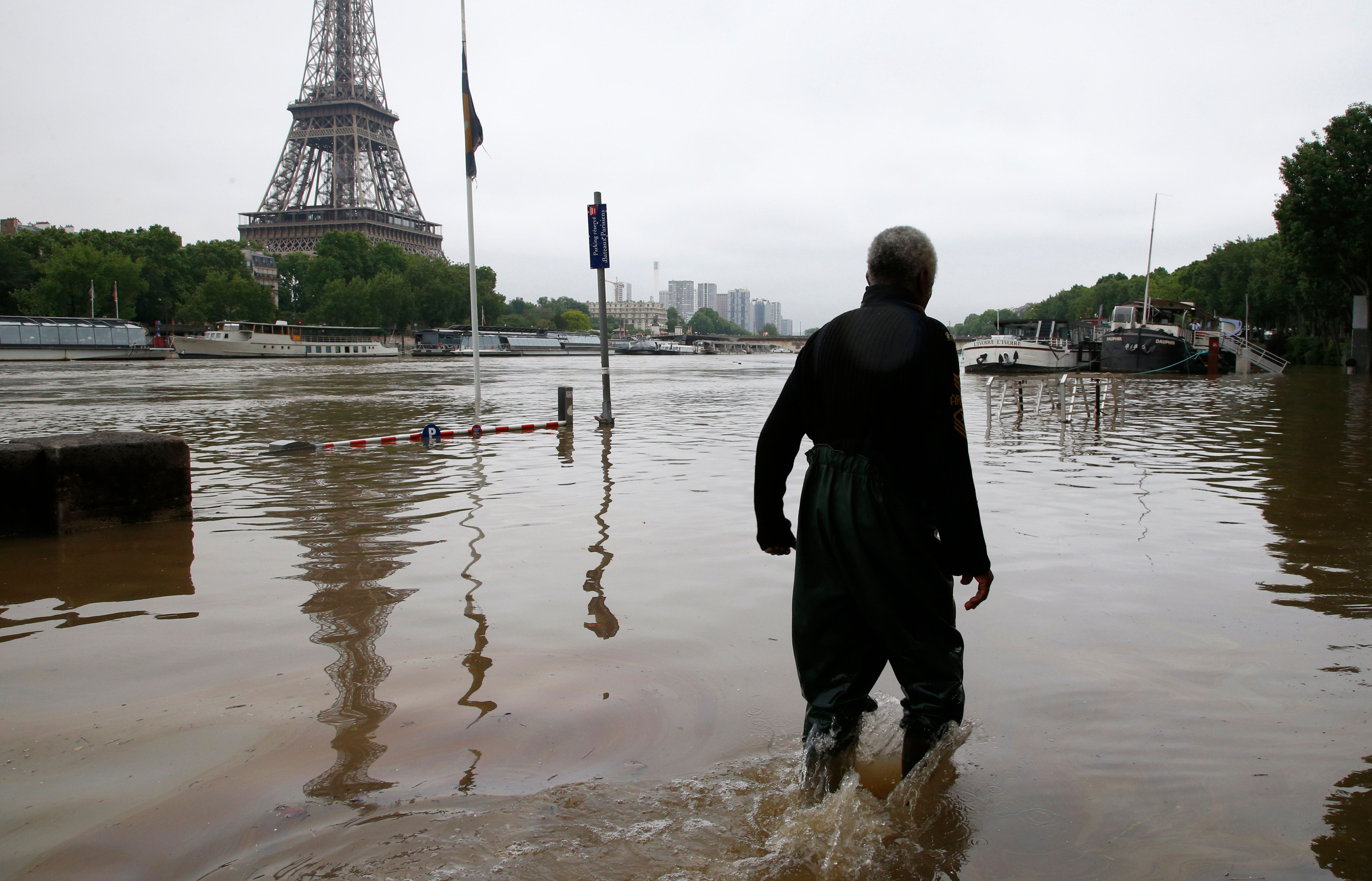 A man walks on a flooded road near his houseboat moored near the Eiffel towel during flooding on the banks of the Seine River in Paris, France, after days of almost non-stop rain caused flooding in the country June 2, 2016. REUTERS/Pascal Rossignol