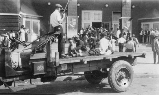 A victim of the Tulsa race riot lays on the back of a flat bed truck outside Convention Hall as a white...