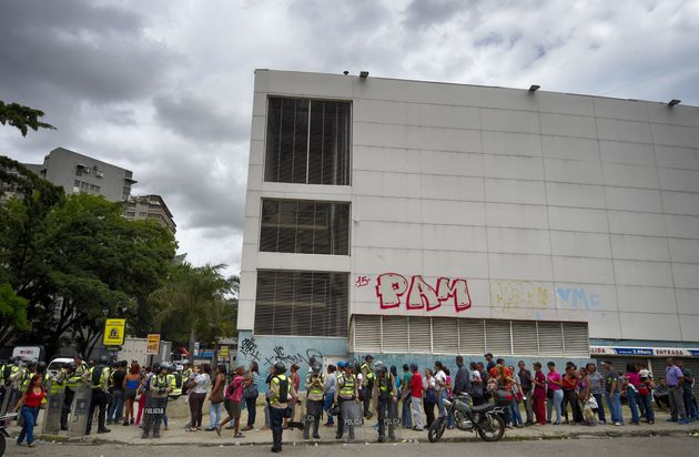 Police stand guard aspeople line up outsidea supermarket in Caracas on June 1, 2016. Basic...