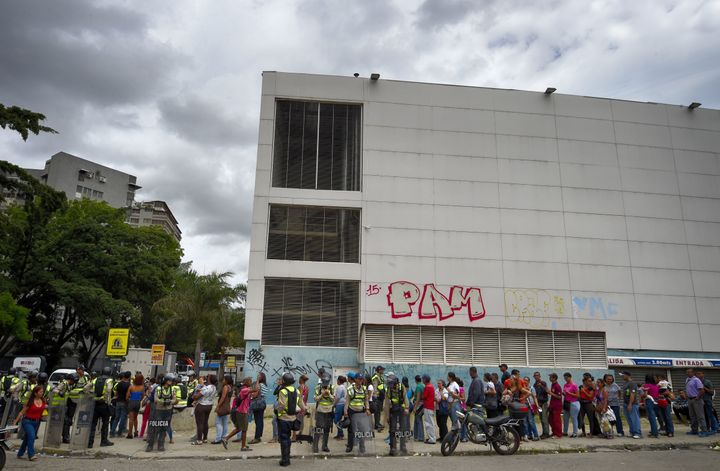 Police stand guard as people line up outside a supermarket in Caracas on June 1, 2016. Basic consumer products, inc