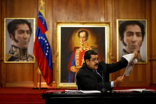 Venezuelan President Nicolás Maduro holds a copy of a newspaper as he speaks in front of images...