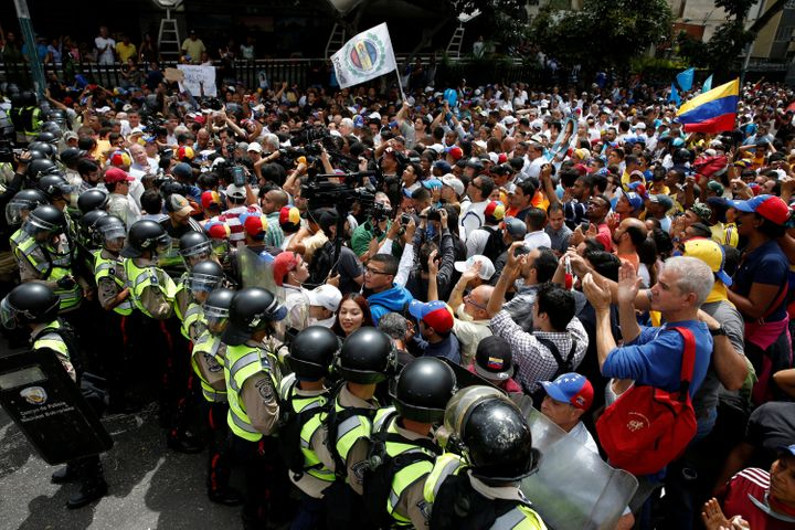 Opposition protesters clash with riot policemen as they demand a referendum to remove President Nicolás Maduro in