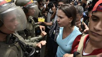Protesters confront Venezuelan National Police officers during a demonstration in support of a referendum on the rule of President Nicolas Maduro in Caracas, Venezuela, on Wednesday, May 18, 2016. Led by two-time presidential candidate Henrique Capriles, demonstrations were held across the country to pressure the electoral board, or CNE, to process a petition to activate a recall referendum. Photographer: Carlos Becerra/Bloomberg via Getty Images