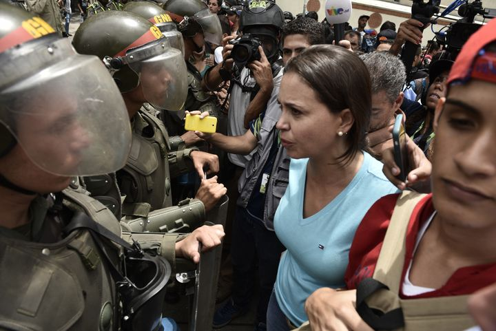 Protesters confront Venezuelan National Police officers during a demonstration fora referendum on the rule of President