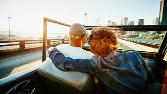 Embracing couple driving convertible on elevated highway along city skyline