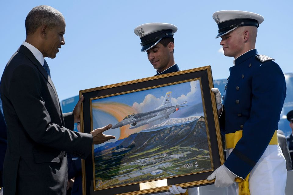 US President Barack Obama is presented a painting during a graduation ceremony at the US Air Force Academy's Falcon Stadium J