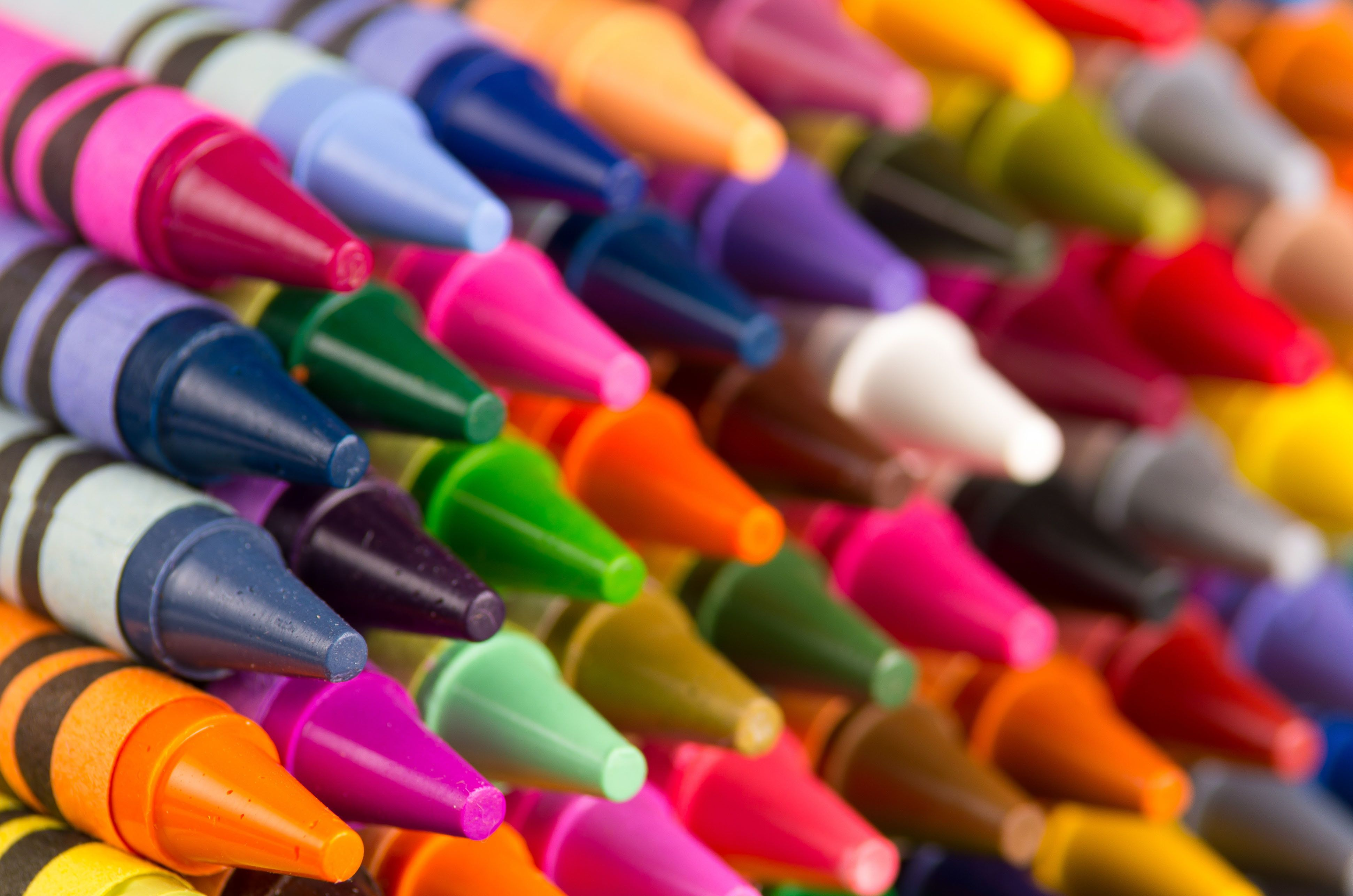 background of multicolored crayons organized in rows closeup