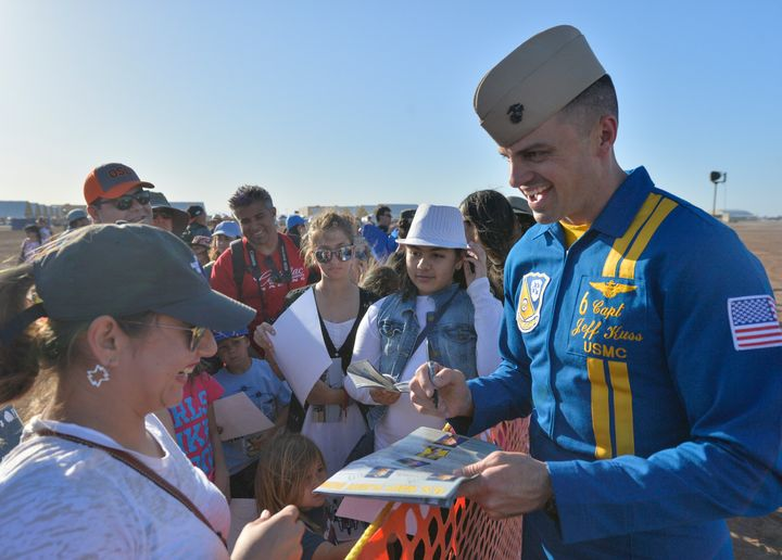 The U.S. Navy Flight Demonstration Squadron, the Blue Angels, opposing solo pilot Capt. Jeff Kuss signs a handout after the d