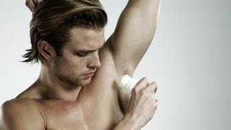 Portrait of man applying deodorant