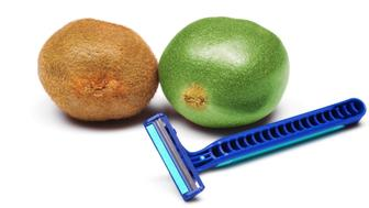 Photo of one cleanly shaven kiwi fruit next to a hairy one.