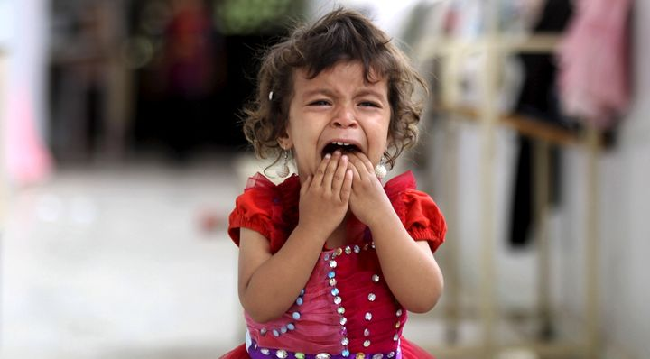 A girl cries at a school sheltering people displaced by Saudi-led air strikes on Yemen's northwestern province of Saada.