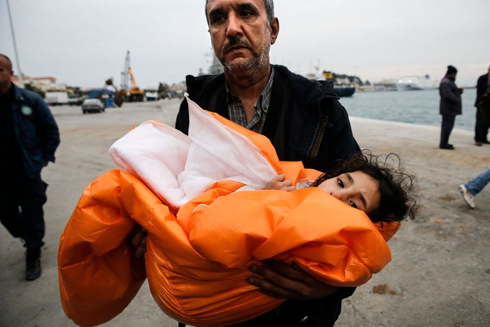 A Syrian refugee carries his daughter covered with a blanket, after being rescued at open sea, as they arrive at the port of