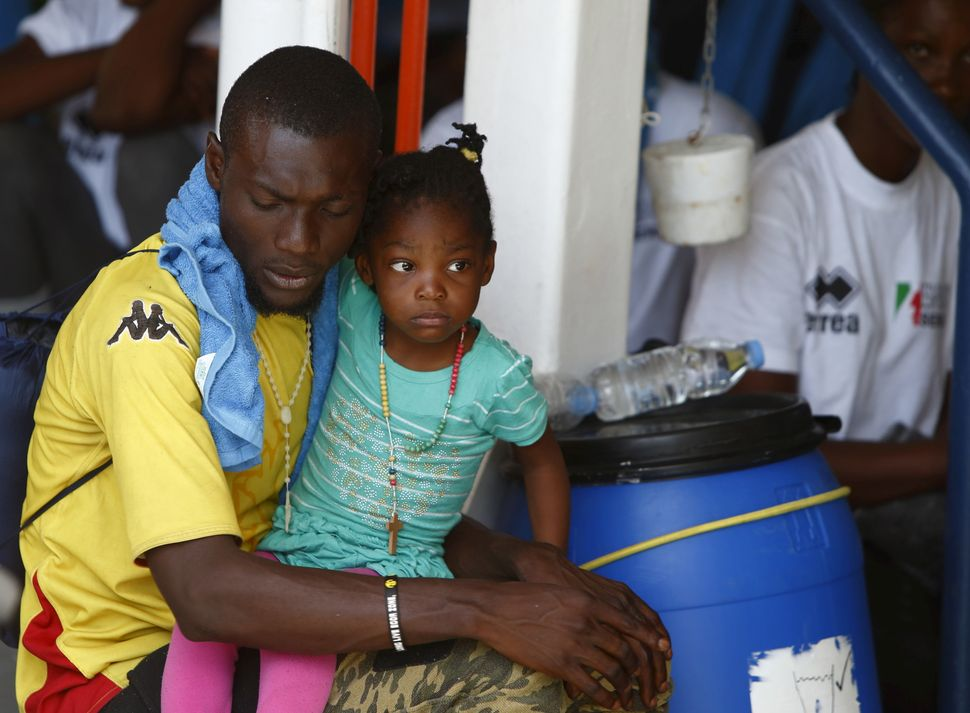 A sub-Saharan migrant holds his child while sitting on the deck of the Migrant Offshore Aid Station ship MV Phoenix in Vibo V