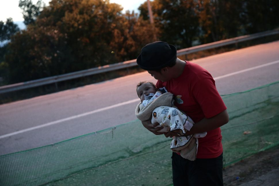 A man with his baby wait at another refugee camp after escaping from a forced evacuation of the camp in Idomeni, Gr