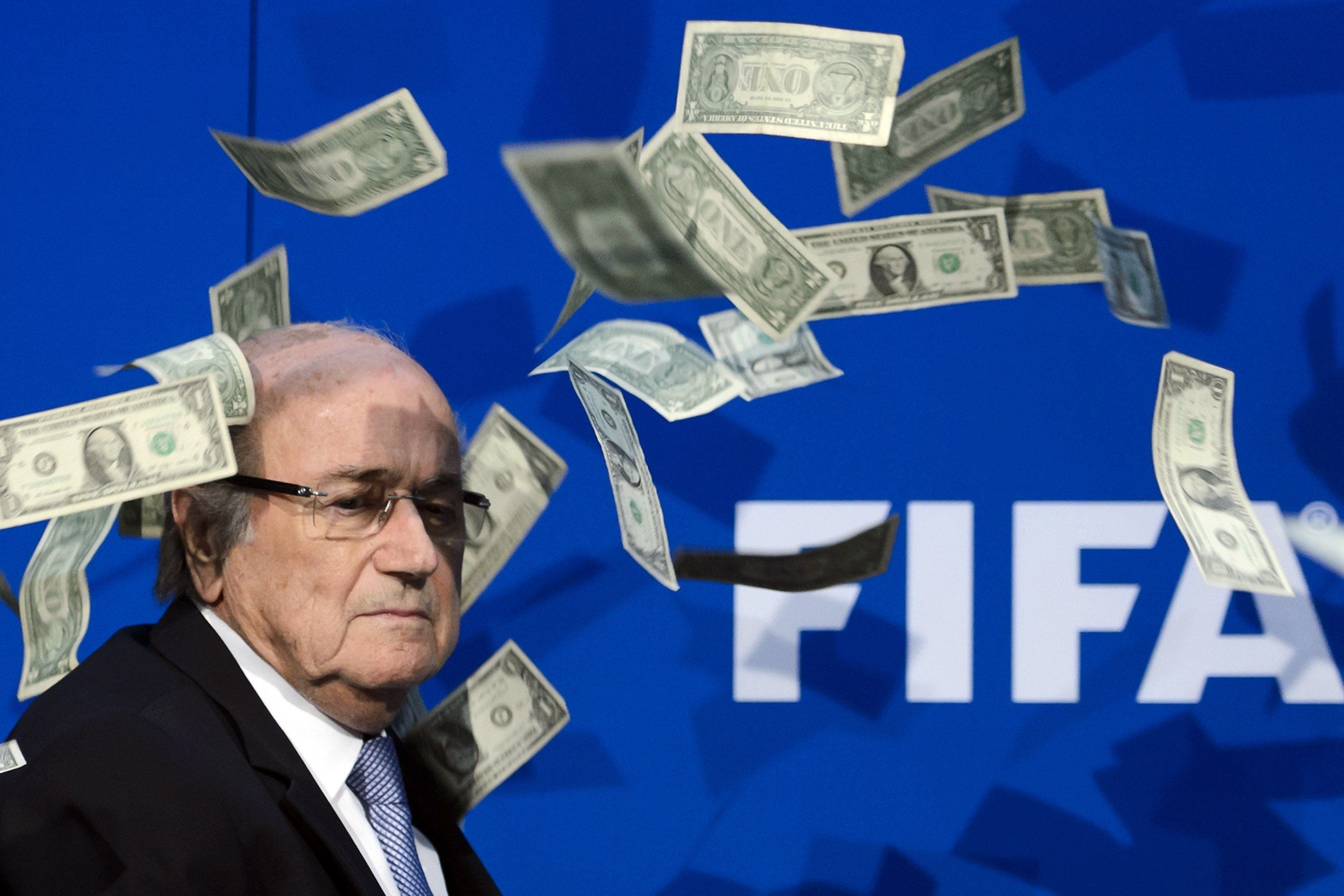 FIFA president Sepp Blatter looks on with fake dollars note flying around him thrown by a protester during a press conference at the football's world body headquarter's on July 20, 2015 in Zurich. FIFA said today that a special election will be held on February 26 to replace president Sepp Blatter.   AFP PHOTO / FABRICE COFFRINI / AFP / FABRICE COFFRINI        (Photo credit should read FABRICE COFFRINI/AFP/Getty Images)