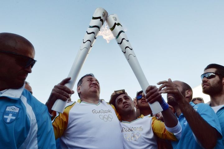 Hellenic Olympic Committee President Spyros Kapralos (2nd L) hands the Olympic Flame to Syrian refugee Ibrahim al-Hussein (C)