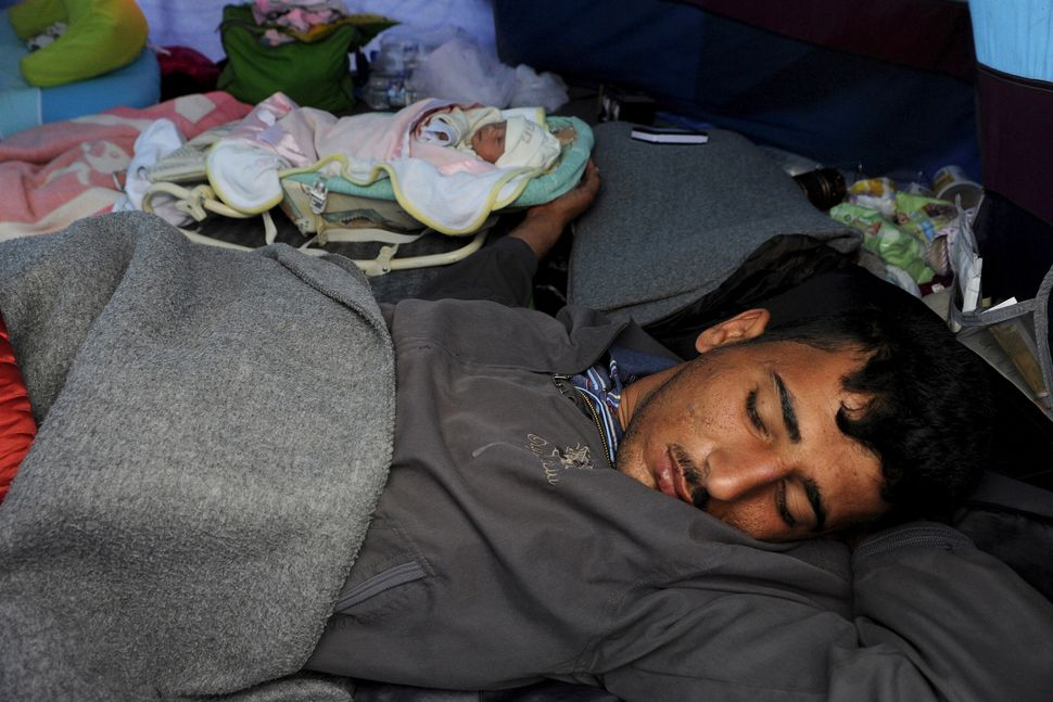 Syrian refugee Saad sleeps next to his 10-day-old daughter, Yasmine, who was born at a Greek hospital in Idomeni.