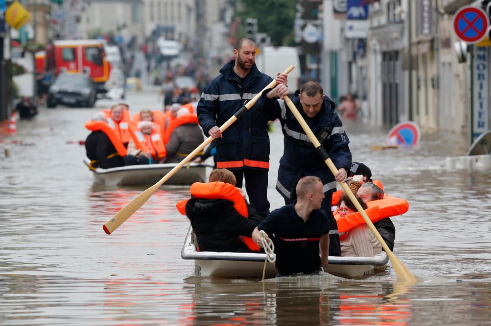French firefighters evacuate residents from a flooded area after heavy rainfall in Nemours, France, on June 1, 2016.