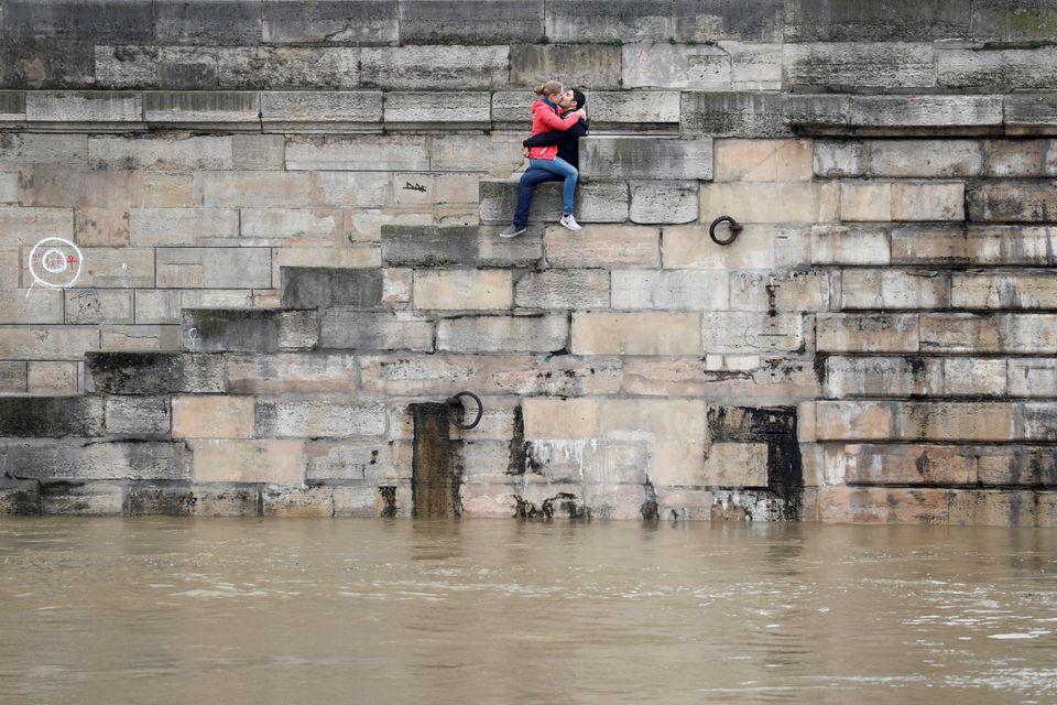 A couple kisses as waterrisesalong the Seine River in Paris on June 1,