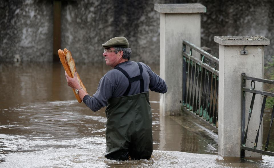 A man brings baguettes to his mother's flooded house in Chalette-sur-Loing Montargis, France, on June...
