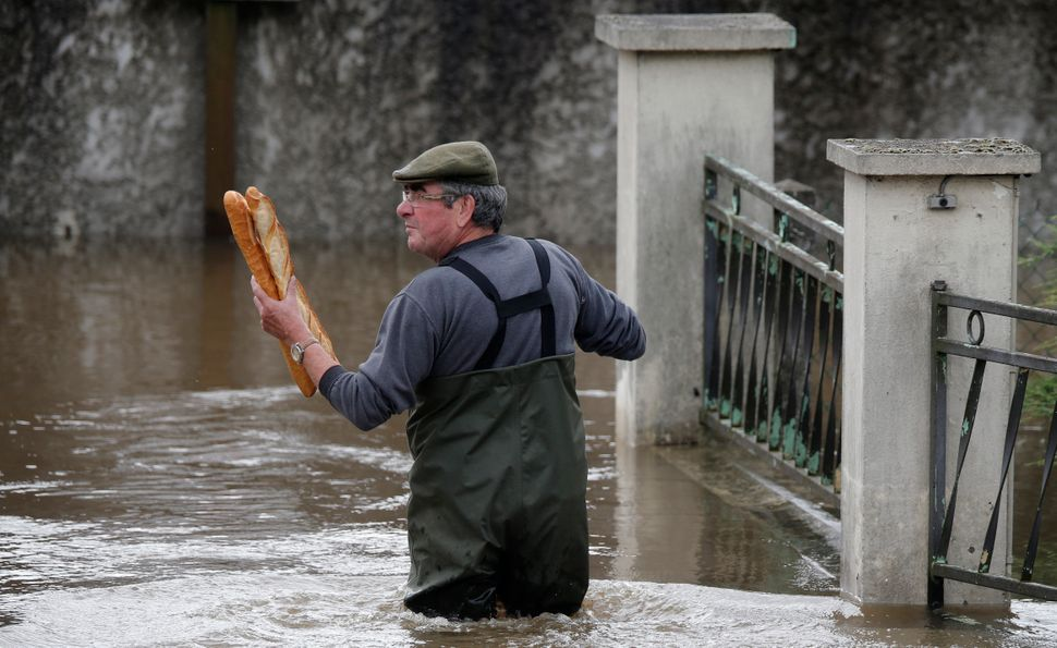 A man brings baguettes to his mother's flooded house in Chalette-sur-Loing Montargis, France, on June 1, 2016.