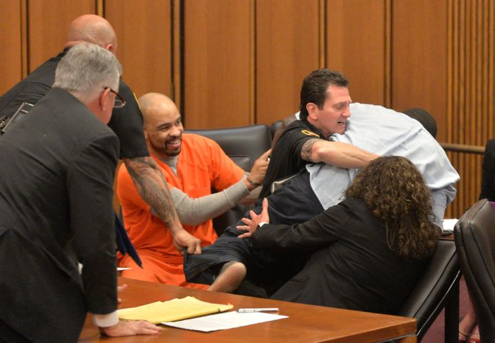 A court officer grabs hold of Van Terry, the grieving father, as killer Michael Madison (in the orange jumpsuit) smiles.