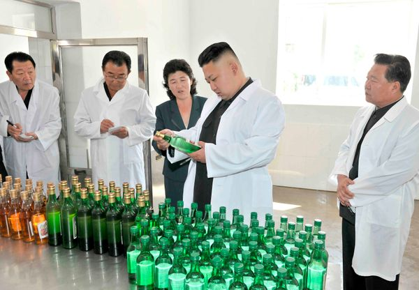 North Korea leader Kim Jong Un looks at bottles of alcohol as he visits the Changsong Foodstuff Factory in June of 2013.