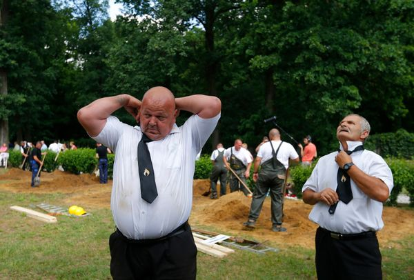 Gravediggers change into their formal clothes after the first Hungarian grave digging championship in Debrecen, Hungary, June