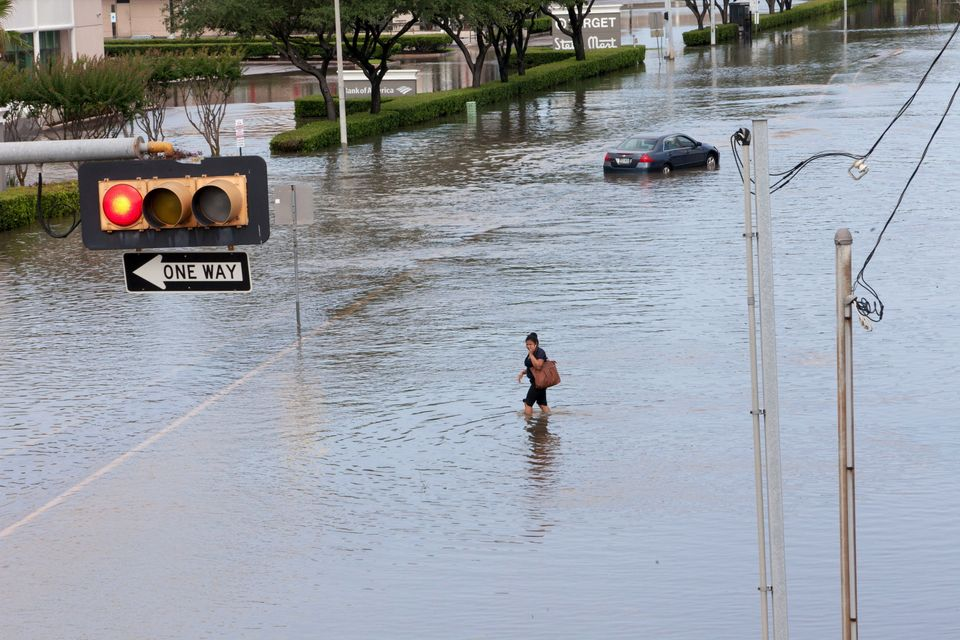 A woman walks in the floodwaters in southwest Houston, Texas, on May 26,