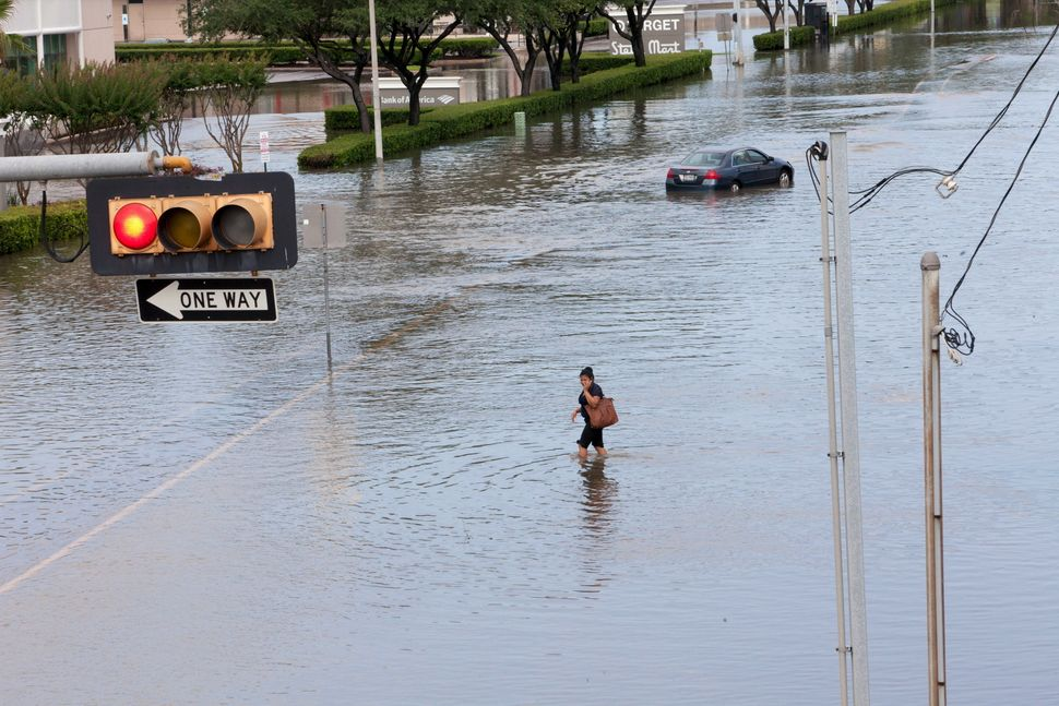 A woman walks in the floodwaters in southwest Houston, Texas, on May 26, 2015.