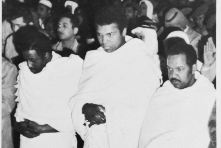 Flanked by fellow pilgrims, Muhammad Ali prays inside a mosque in Mecca during a pilgrimage to the spiritual center