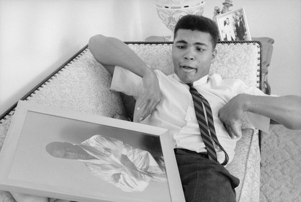 Muhammad Ali, then known as Cassius Clay, lies on a couch and clowns around with a framed photograph of then-heavyweight cham